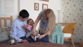 Χαμογελώντας οικογένεια στο κρεβάτι όπου ο μπαμπάς και mom φορά τις κάλτσες με τη μικρή κόρη τους φιλμ μικρού μήκους