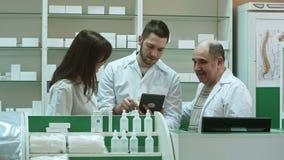 Χαμογελώντας ομάδα των φαρμακοποιών, δύο αρσενικός και ένα θηλυκό, στάση δίπλα-δίπλα στο φαρμακείο που ελέγχει τις πληροφορίες γι φιλμ μικρού μήκους