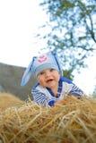 Χαμογελώντας παιδί σε ένα κοστούμι λαγουδάκι που χαμογελά και που θέτει στο άχυρο στοκ εικόνες με δικαίωμα ελεύθερης χρήσης