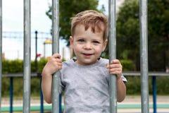Χαμογελώντας παιδί στο υπόβαθρο φρακτών στοκ εικόνα με δικαίωμα ελεύθερης χρήσης