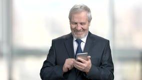Χαμογελώντας παλαιότερος επιχειρηματίας με το smartphone απόθεμα βίντεο