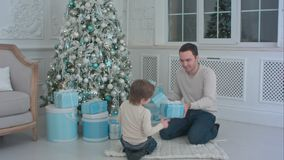 Χαμογελώντας πατέρας και τα ανοίγοντας χριστουγεννιάτικα δώρα γιων του στο καθιστικό στοκ εικόνες