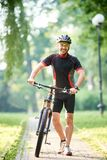 Χαμογελώντας ποδηλάτης που περπατά κοντά στο ποδήλατο κάτω από την αλέα Στοκ Εικόνες