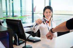 Χαμογελώντας ρεσεψιονίστ που ανιχνεύει το έξυπνο ρολόι του επιβάτη σε Airpor Στοκ Εικόνα