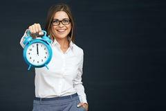 Χαμογελώντας ρολόι εκμετάλλευσης επιχειρησιακών γυναικών Στοκ εικόνες με δικαίωμα ελεύθερης χρήσης
