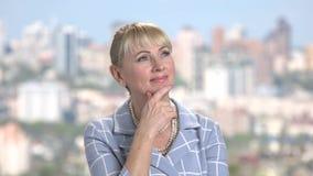 Χαμογελώντας σκεπτόμενη γυναίκα στο θολωμένο υπόβαθρο απόθεμα βίντεο