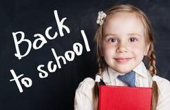 Χαμογελώντας σπουδαστής μικρών κοριτσιών πίσω σχολείο εμβλημάτων στοκ φωτογραφία