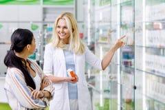 χαμογελώντας τα εμπορευματοκιβώτια εκμετάλλευσης φαρμακοποιών με το φάρμακο και συμβουλευτικός τον πελάτη στοκ φωτογραφίες με δικαίωμα ελεύθερης χρήσης