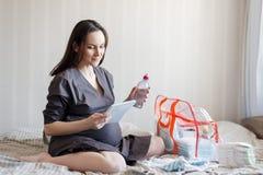 Χαμογελώντας τη συνεδρίαση εγκύων γυναικών στο κρεβάτι με έναν κατάλογο στα χέρια του, συλλέγει τα πράγματα στην τσάντα για το νο στοκ εικόνα