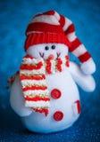 Χαμογελώντας το παιχνίδι χιονανθρώπων που ντύνεται στο μαντίλι και την ΚΑΠ στο αφηρημένο υπόβαθρο bokeh Στοκ εικόνες με δικαίωμα ελεύθερης χρήσης