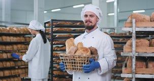 Χαμογελώντας χαρισματικός αρτοποιός ατόμων με ένα μεγάλο σύνολο καλαθιών του φρέσκου ψημένου ψωμιού που φαίνεται ευθέος στη κάμερ απόθεμα βίντεο