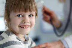 Χαμογελώντας χαριτωμένος λίγο ασθενή που αλληλεπιδρά με το θηλυκό γιατρό στοκ φωτογραφία