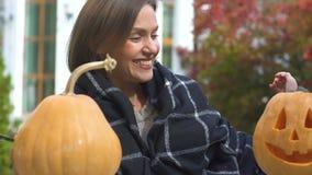 Χαμογελώντας χαριτωμένο κορίτσι που παρουσιάζει mom χαρασμένη κολοκύθα Jack-ο-φαναριών, κόμμα παραμονής αποκριών απόθεμα βίντεο