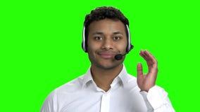 Χαμογελώντας χειριστής τηλεφωνικών κέντρων στην πράσινη οθόνη φιλμ μικρού μήκους