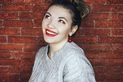 Χαμογελώντας όμορφες γυναίκες που ανατρέχουν, φορώντας το γκρίζο πουλόβερ του ST και τα κόκκινα σκουλαρίκια, με τα κόκκινα χείλια στοκ φωτογραφίες