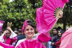 Χαμογελώντας όμορφη γυναίκα με έναν ροζ ανεμιστήρα χεριών και ρόδινο κοστούμι στο άνοιγμα της πορτοκαλιάς ανθών παρέλασης καρναβα στοκ φωτογραφία