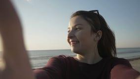 Χαμογελώντας όμορφη γυναίκα με τα γυαλιά ηλίου που παίρνουν selfie χρησιμοποιώντας το τηλέφωνο στην παραλία περιστρέφοντας και απ φιλμ μικρού μήκους
