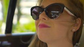 Χαμογελώντας όμορφη γυναίκα που απολαμβάνει τη θέα από το παράθυρο αυτοκινήτων, ηλιόλουστος καιρός, αέρας στην τρίχα απόθεμα βίντεο