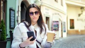 Χαμογελώντας όμορφη γυναίκα που κουβεντιάζει χρησιμοποιώντας τον καφ απόθεμα βίντεο