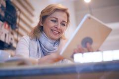 Χαμογελώντας όμορφη γυναίκα που χρησιμοποιεί την ταμπλέτα Στοκ Φωτογραφία