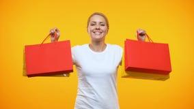 Χαμογελώντας όμορφη κυρία που παρουσιάζει τσάντες αγορών στο πορτοκαλί υπόβαθρο, πώληση διακοπών φιλμ μικρού μήκους
