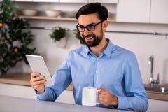 Χαμογελώντας όμορφος επιχειρηματίας που χρησιμοποιεί την ταμπλέτα του στοκ φωτογραφίες