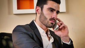 Χαμογελώντας όμορφος νέος επιχειρηματίας στο γραφείο στο τηλέφωνο Στοκ Φωτογραφίες