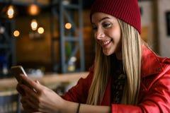 Χαμογελώντας όμορφο αστικό κορίτσι που χρησιμοποιεί το έξυπνος-τηλέφωνο έξω στην καφετέρια στοκ φωτογραφίες