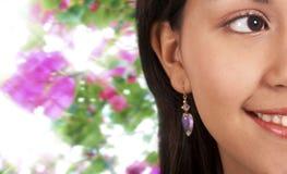 Χαμογελώντας όμορφο κορίτσι με την ανασκόπηση λουλουδιών Στοκ Φωτογραφίες