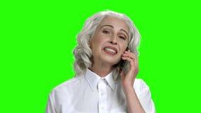 Χαμογελώντας ώριμη γυναίκα στο πράσινο υπόβαθρο οθόνης απόθεμα βίντεο