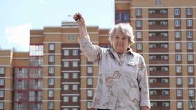 Χαμογελώντας ώριμη ηλικιωμένη γυναίκα που αυξάνει το χέρι επάνω με τα κλειδιά φιλμ μικρού μήκους