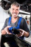 Χαμογελώντας ώριμο άτομο που κρατά το φίλτρο πετρελαίου ενός αυτοκινήτου στοκ φωτογραφίες με δικαίωμα ελεύθερης χρήσης