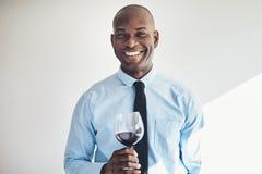 Χαμογελώντας ώριμο άτομο που πίνει ένα ποτήρι του κόκκινου κρασιού Στοκ εικόνα με δικαίωμα ελεύθερης χρήσης