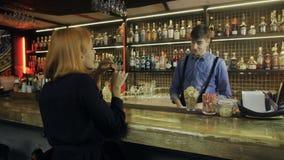 Χαμογελώντας bartender χύνοντας ποτά και ομιλία στον εύθυμο επισκέπτη στο  φιλμ μικρού μήκους