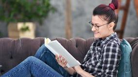 Χαμογελώντας hipster νέο κορίτσι που φορά τα γυαλιά που διαβάζουν τη συνεδρίαση βιβλίων στο μέσο πυροβολισμό καναπέδων στο σπίτι φιλμ μικρού μήκους