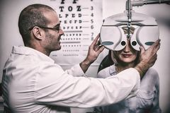 Χαμογελώντας optometrist που εξετάζει το θηλυκό ασθενή στο phoropter στοκ φωτογραφίες