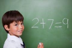 Χαμογελώντας schoolboy που γράφει μια προσθήκη Στοκ εικόνα με δικαίωμα ελεύθερης χρήσης