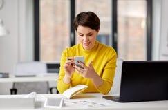 Χαμογελώντας ui σχεδιαστής που χρησιμοποιεί το smartphone στο γραφείο στοκ φωτογραφίες