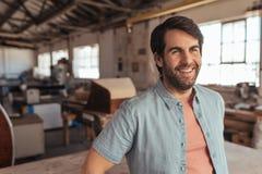 Χαμογελώντας woodworker που κλίνει σε έναν πίνακα στο στούντιο ξυλουργικής του Στοκ Φωτογραφίες