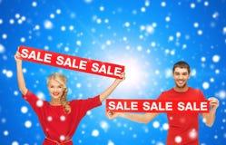 Χαμογελώντας άνδρας και γυναίκα με τα κόκκινα σημάδια πώλησης Στοκ Φωτογραφίες