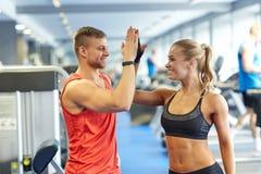 Χαμογελώντας άνδρας και γυναίκα που κάνουν υψηλά πέντε στη γυμναστική Στοκ Φωτογραφίες