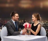 Χαμογελώντας άνδρας που δίνει την ανθοδέσμη λουλουδιών στη γυναίκα Στοκ εικόνα με δικαίωμα ελεύθερης χρήσης
