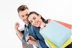 Χαμογελώντας άνδρας που εξετάζει τη γυναίκα με τις τσάντες αγορών στο λευκό Στοκ Φωτογραφίες