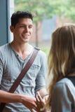 Χαμογελώντας άνδρας σπουδαστής που μιλά σε έναν φίλο Στοκ εικόνα με δικαίωμα ελεύθερης χρήσης