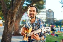 Χαμογελώντας άτομο με την κιθάρα στον εορτασμό υπαίθρια Στοκ Φωτογραφίες