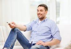 Χαμογελώντας άτομο με τον τηλεχειρισμό TV στο σπίτι Στοκ φωτογραφία με δικαίωμα ελεύθερης χρήσης