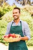 Χαμογελώντας άτομο με το καλάθι μήλων που κοιτάζει μακριά Στοκ Εικόνες