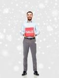 Χαμογελώντας άτομο με το κόκκινο σημάδι πώλησης πέρα από το χιόνι Στοκ Φωτογραφία