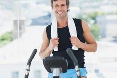 Χαμογελώντας άτομο που επιλύει στην περιστροφή της κατηγορίας στη φωτεινή γυμναστική στοκ εικόνα