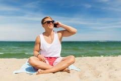Χαμογελώντας άτομο που καλεί το smartphone στη θερινή παραλία Στοκ φωτογραφία με δικαίωμα ελεύθερης χρήσης